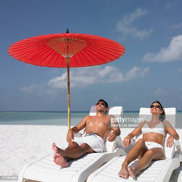 Couple sunbathing on the beach