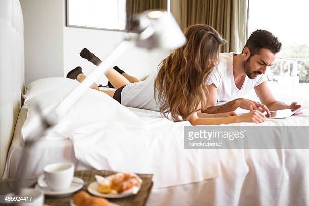 couple surfing with tablet lying down on the bed