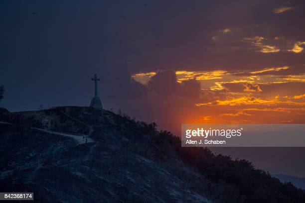 A couple survey the damage as they walk near a cross that remains standing amid the scorched hillside that destroyed three homes and a shed and is...