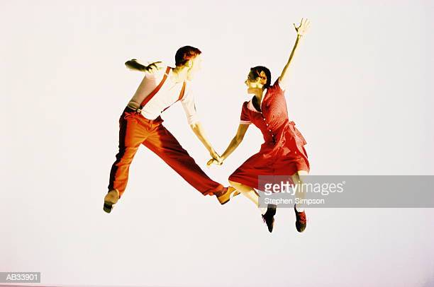 Couple swing dancing in mid air