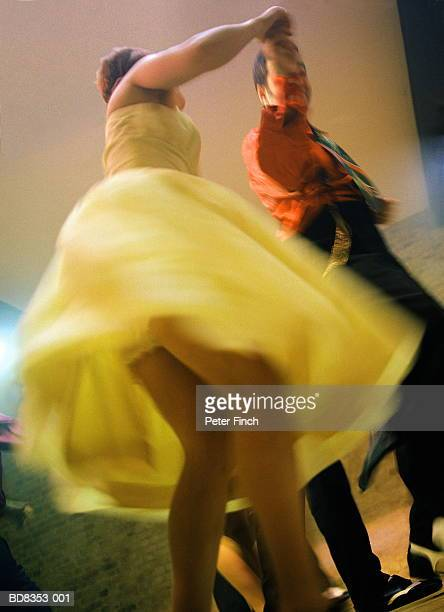 Couple swing dancing, woman in yellow dress (blurred motion)