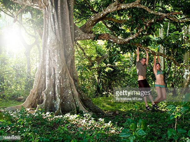 Couple swinging on banyan tree in Fiji
