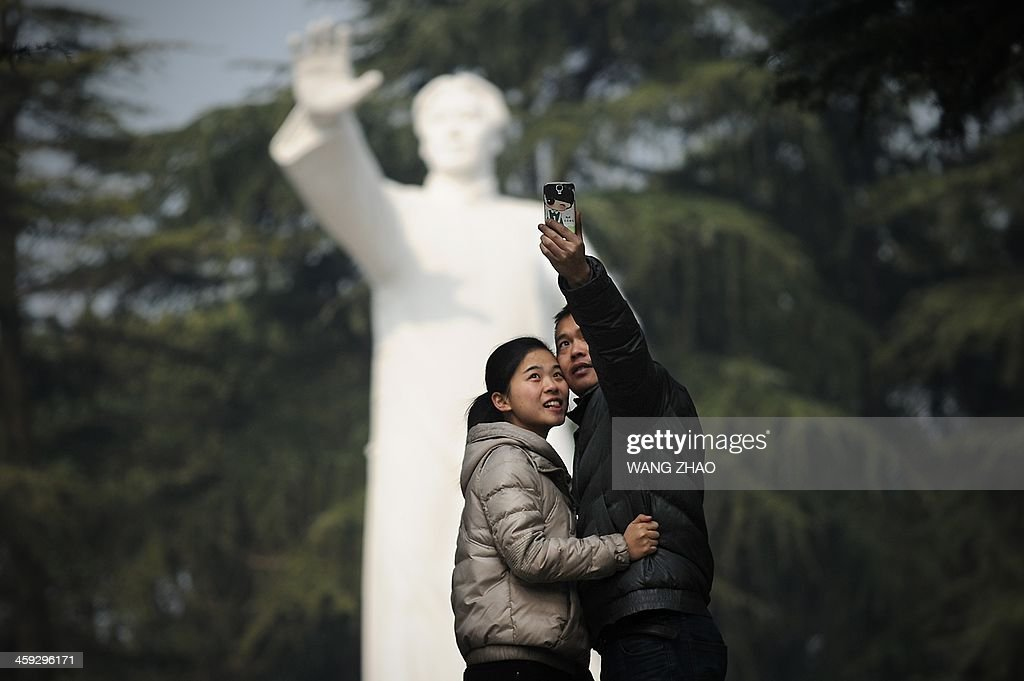 A couple take a photo in front of a statue of former Chinese leader Mao Zedong at a park in Shaoshan, in China's central province of Hunan on December 25, 2013. Thousands of admirers of Communist China's founder Mao Zedong flocked to his home town on December 25 to bow before his graven image -- including one statue of solid gold -- before the 120th anniversary of his birth.