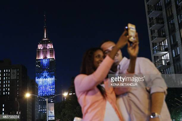 A couple take a selfie as they watch a projection on the Empire State Building called the 'Projecting Change on the Empire State Building' project...