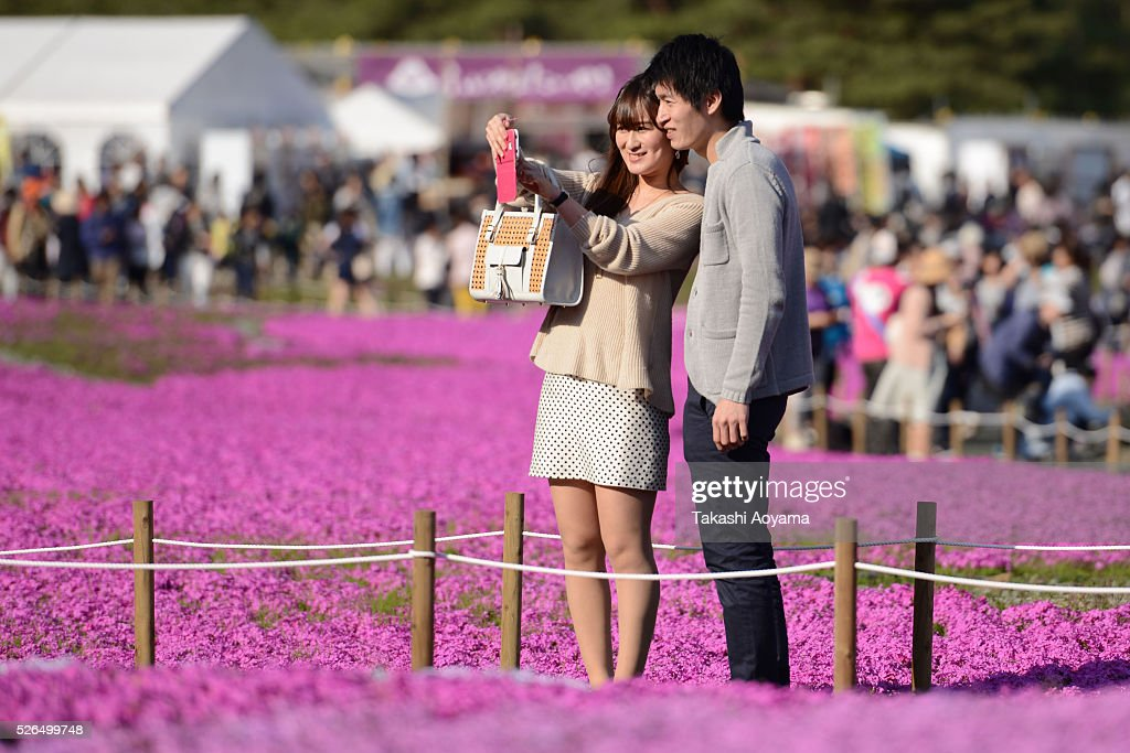 A couple take a selfie in front of full bloom Shibazakura (Moss phlox) during the Fuji Shibazakura Festival at Ryujin-ike Pond on April 30, 2016 in Fujikawaguchiko, Japan. About 800,000 mos phlox flowers are in full bloom at the festival held near the Mt. Fuji.