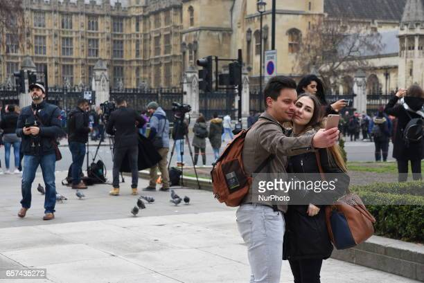 A couple take a selfie in front of the Houses of Parliament from the south side of the River Thames on March 24 2017 in London England A fourth...