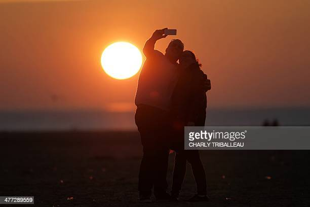 A couple take a selfie photograph at sunset in Deauville northwestern France on March 8 2014 AFP PHOTO/CHARLY TRIBALLEAU