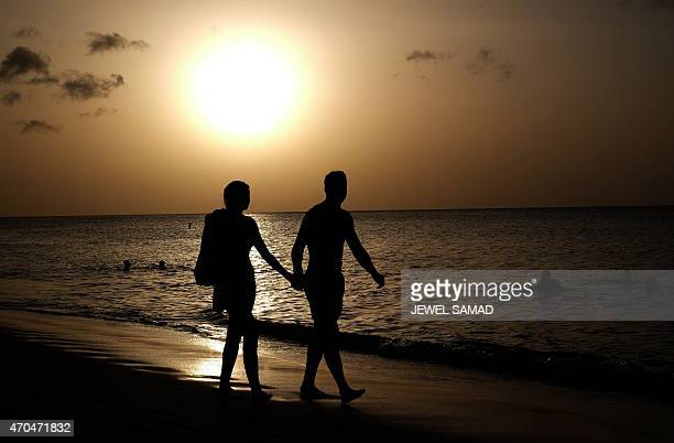 A couple take a stroll along a beach in Saint George's Grenada on April 20 2015 AFP PHOTO/JEWEL SAMAD