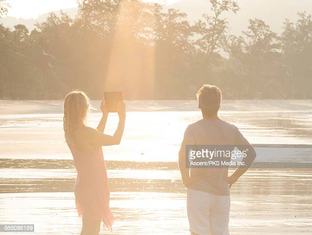 Couple take digital tablet picture on beach, sun