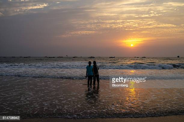 A couple take photographs of the sunset at Baga beach in Bardez Goa India on Wednesday March 9 2016 While India is forecast to overtake a slowing...