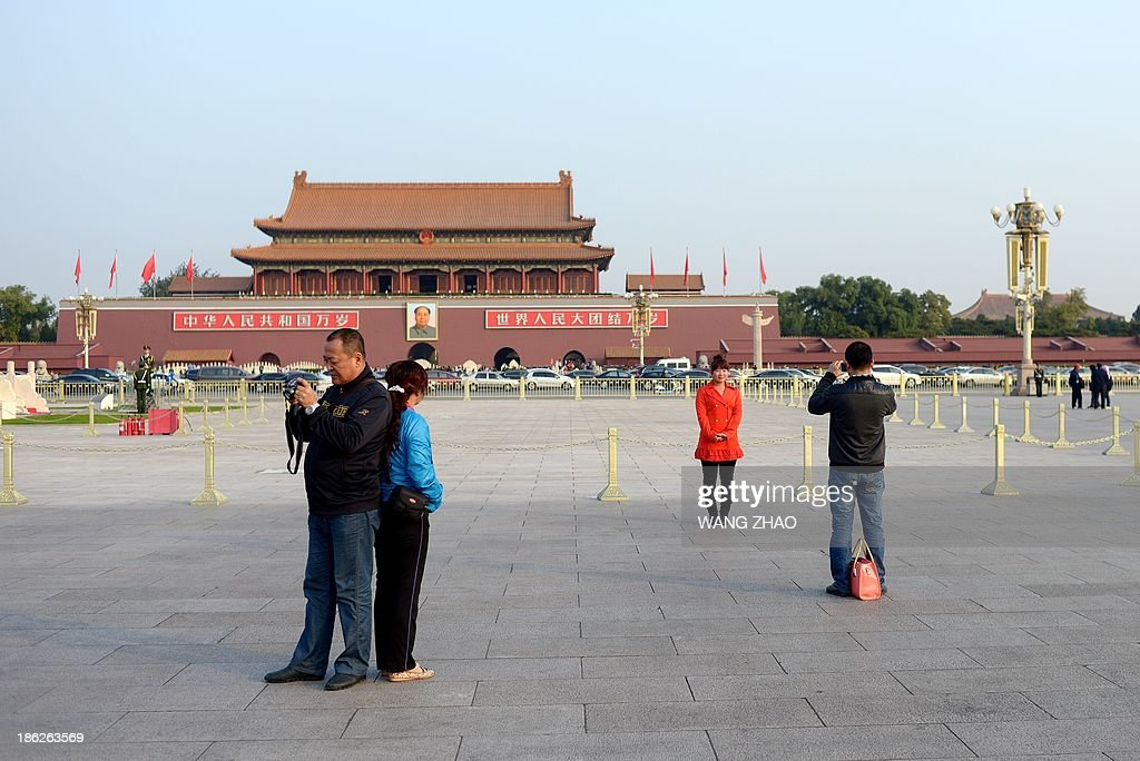 A couple (R) take photos at Tiananmen square in Beijing on October 30, 2013. Police in Beijing are searching for eight suspects from China's restive Xinjiang region after a fatal car crash in Tiananmen Square, hotel staff said on October 30, as a minority rights group expressed fears of a crackdown.