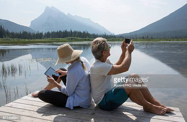 Couple take pic and use digital tablet, mtn lake