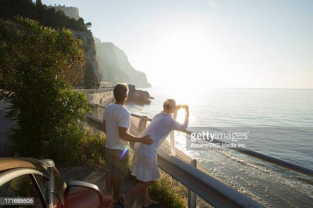 Couple take picture by car, along coastal road