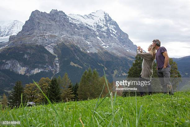 Couple take picture in meadow, mountains