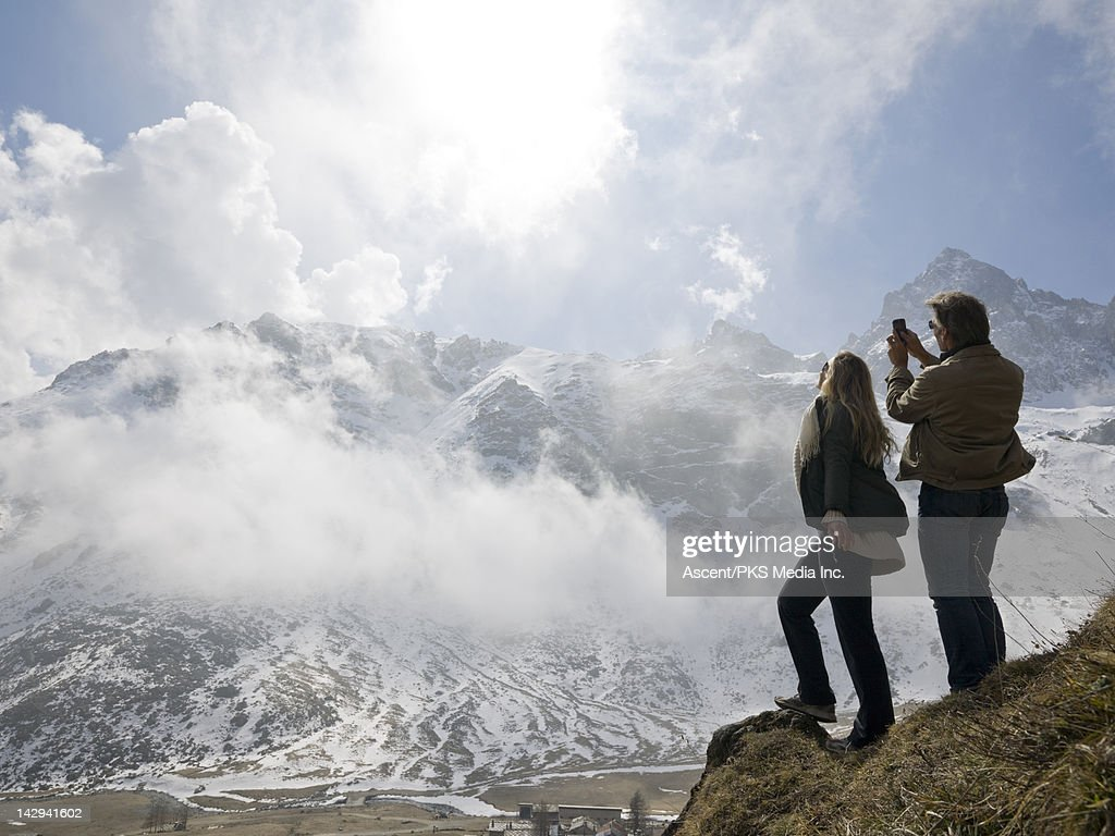 Couple take picture of drifting clouds, in mtns : Stock Photo