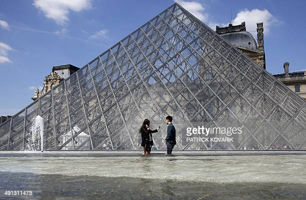 A couple take pictures near the Louvre Museum pyramid on May 16 2014 in Paris AFP PHOTO / PATRICK KOVARIK