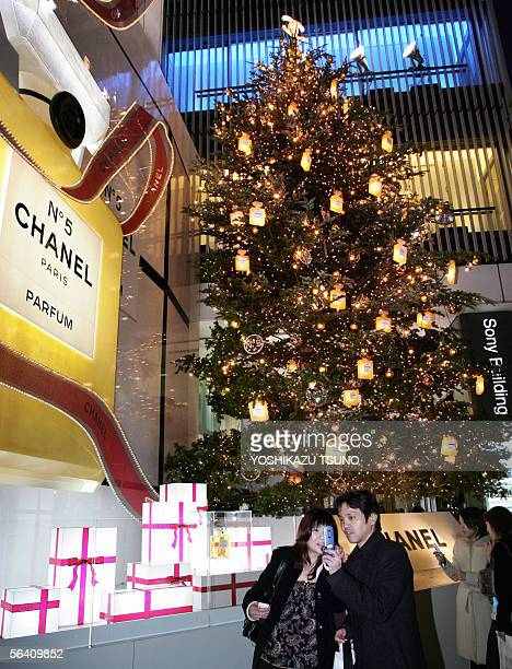 A couple take pictures of a large Christmas tree decorated with elecric bulbs shaped Chanel No 5 perfume bottles as a Christmas decoration inside...