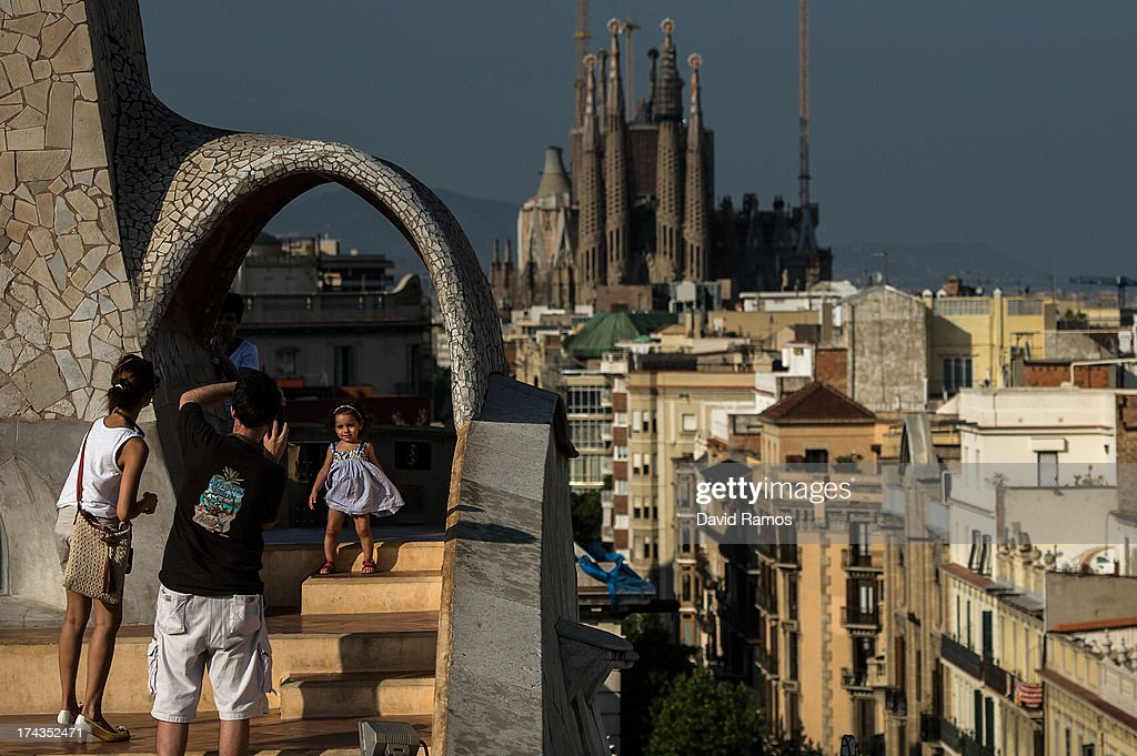 A couple take pictures of their daughter at the roof of the building 'La Pedrera' or 'Casa Mila' of Antoni Gaudi with La Sagrada Familia on the background on July 24, 2013 in Barcelona, Spain. Foreign visitors to Spain set a new record high in June surpassing six million tourists for the first time ever and climbing by 5.3 percent since June 2012.
