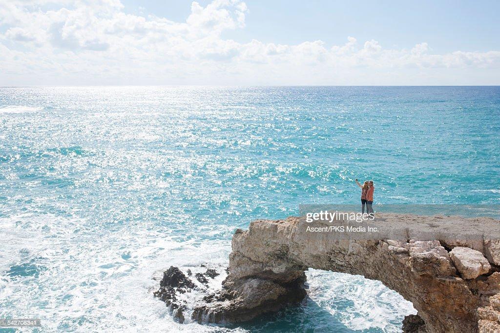 Couple take selfie pic on natural bridge, sea surf