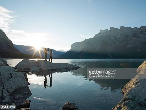 Couple take smart phone pic by lake edge, sunrise