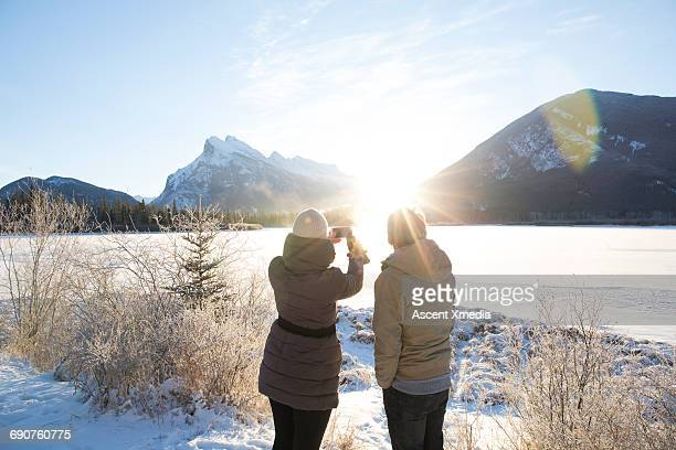 Couple take smart phone pic on frozen lake, mtns