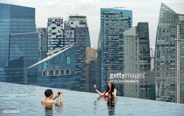 A couple take their photograph from the rooftop pool of Marina Bay Sands resort hotel overlooking the city skyline in Singapore on May 20 2014...