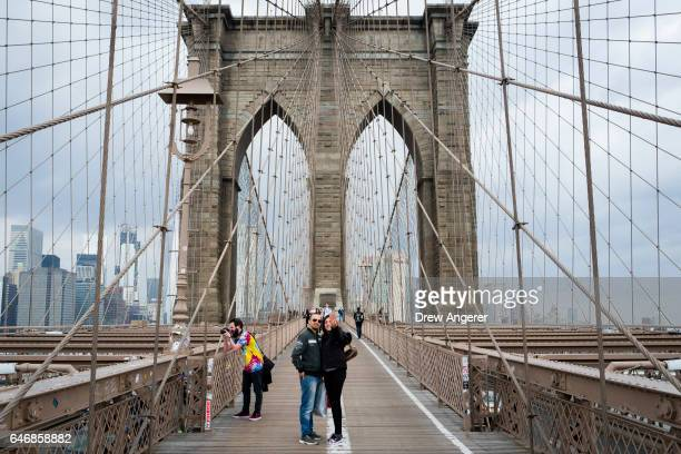 A couple takes a photograph of themselves on the Brooklyn Bridge March 1 2017 in New York City NYC Company the city's tourism marking agency released...