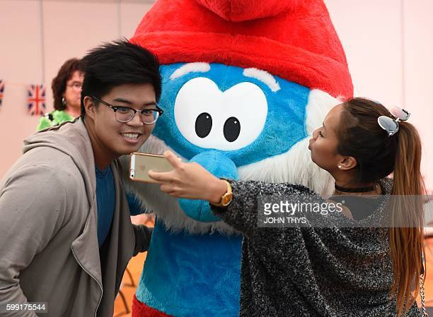 A couple takes a selfie with Papa Smurf during the festival 'Fete de la BD' in Brussels on September 2 2016 The comic strip festival 'Fete de la BD'...