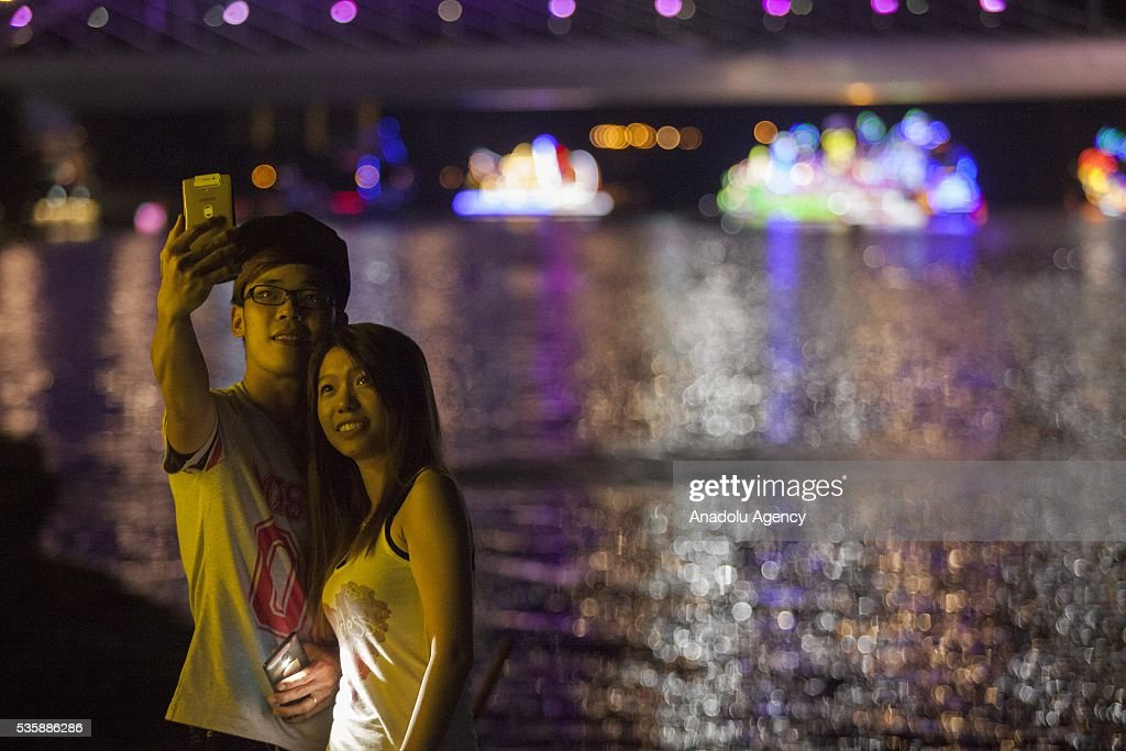A couple takes a selfie with the colorful decorated boats repre the states of Malaysia during the Magic Of The Night event at Royal Floria flower festival in Putrajaya, Malaysia on May 30, 2016.