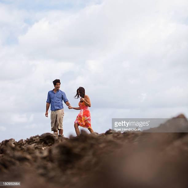 A couple takes a walk on lava rock