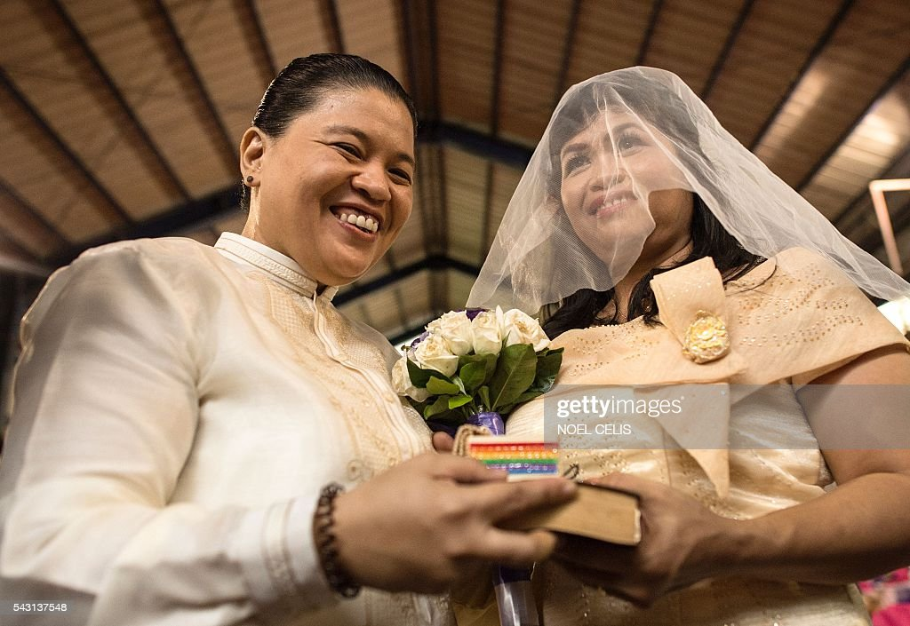 A couple takes part in a 'Rite of Holy Union' as members of the lesbian, gay, bisexual and transgender (LGBT) community gather in Manila on June 26, 2016, for a ceremony that coincided with Gay Pride celebrations the day before. The Philippines has a vibrant gay scene despite a macho culture and opposition from the Roman Catholic Church, but there are no anti-discrimination laws in the country and same-sex relationships are not officially recognised. / AFP / NOEL