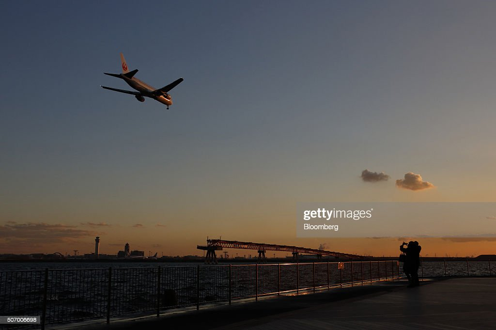 A couple takes photographs of a Japan Airlines Corp aircraft approaching to land at Haneda Airport at dusk in Tokyo Japan on Tuesday Jan 26 2016 JAL...