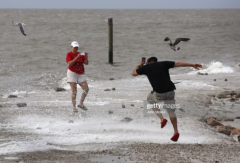 A couple takes photos as hurricane Isaac churns the surf on August 28, 2012 in Bay St. Louis, Mississippi. Many residents of the area decided to stay in their homes instead of evacuate ahead of the arrival of the Level 1 hurricane. The area was devestated by Hurricane Katrina in 2005.