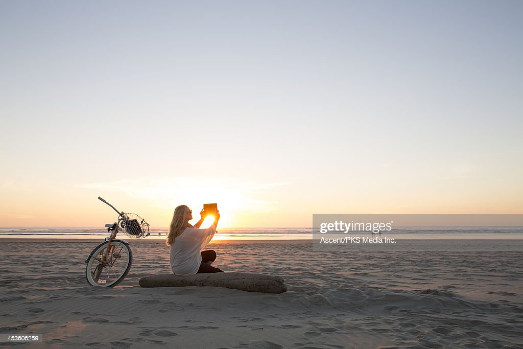 Couple takes picture with digital tablet, beach