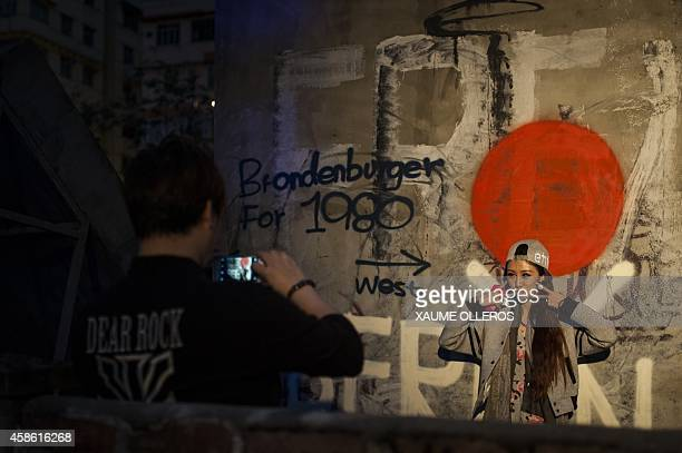 A couple takes pictures in front of a Berlin wall graffiti replica at the Berlin Fest at Cattle Depot Artist Village in Hong Kong on November 8 2014...