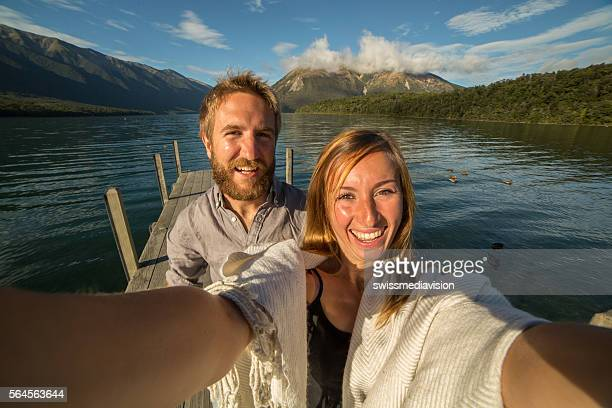 Couple takes selfie portrait on lake pier