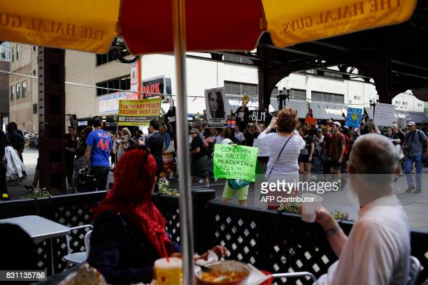 A couple taking a meal watch as demonstrators protest against hate white supremacy groups and President Donald Trump on Sunday August 13 2017 in...
