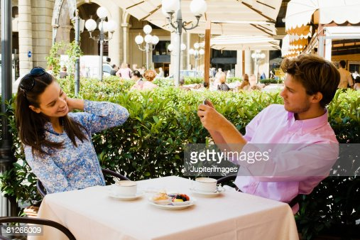 Couple taking a picture at outdoor cafe : Stock Photo