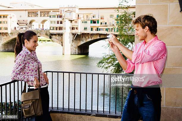 Couple taking a picture near Arno River and Ponte Vecchio, Florence, Italy