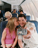 Couple Taking a Picture of Themselves in an Airplane, Woman Kissing the Man on His Cheek