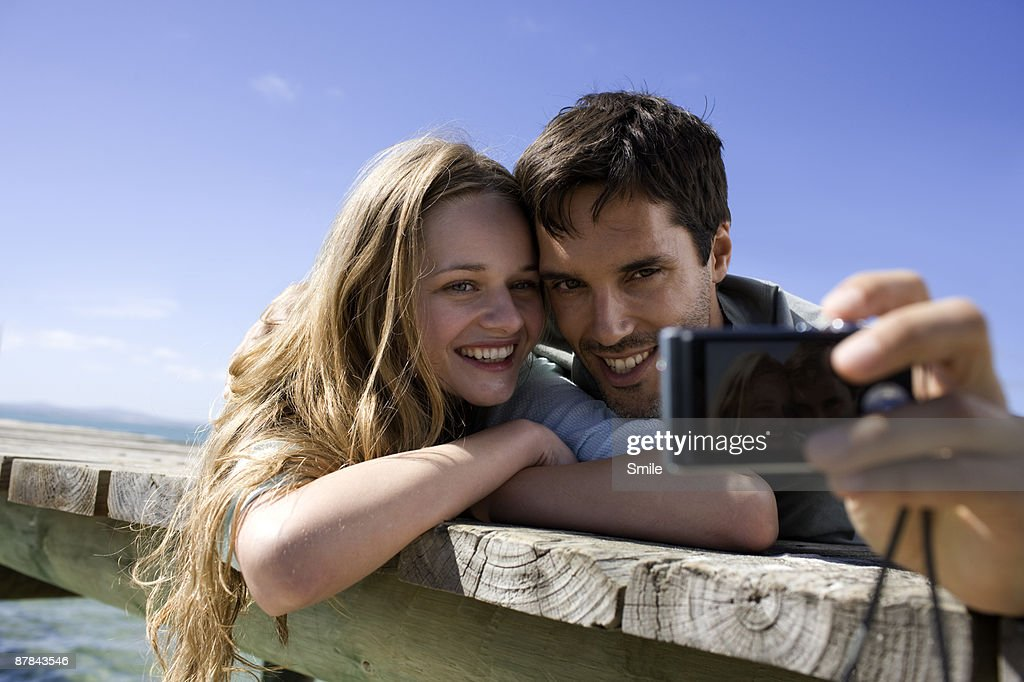couple taking a picture of themselves on jetty : Stock Photo