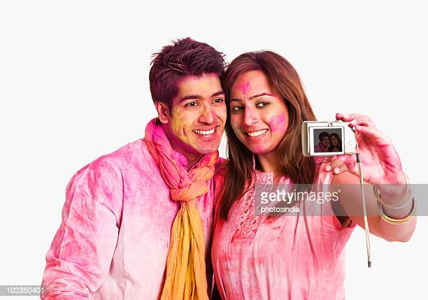 Couple taking a picture of themselves with a camera on Holi