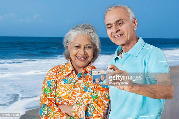 Couple taking a picture of themselves with a digital camera on the beach
