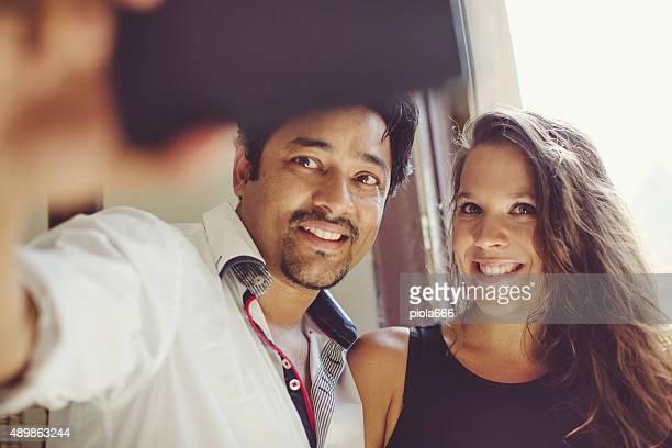Couple taking a selfie by a window