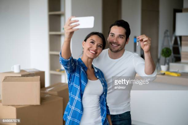 Couple taking a selfie holding keys to their new house