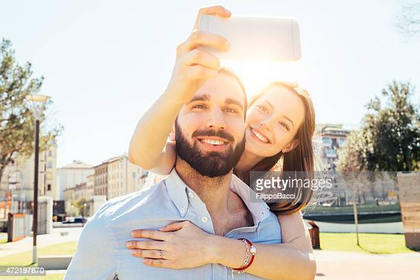 Couple taking a selfie in the city park on a sunny day