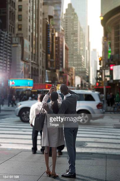 Couple taking cellphone picture of Times Square
