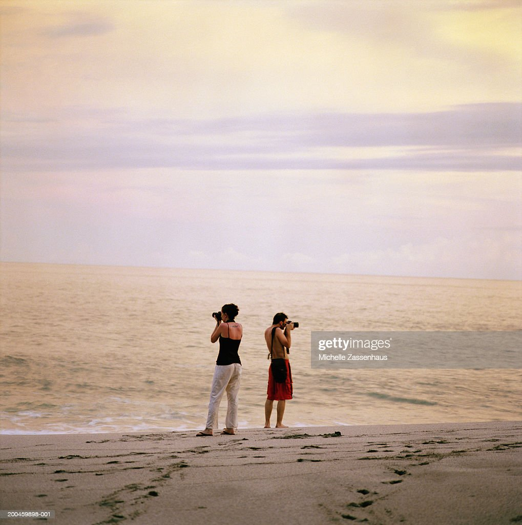 Couple Taking Digital Photos At Beach Sunset Stock Photo