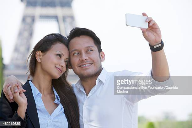 Couple taking photo of themselves by Eiffel Tower