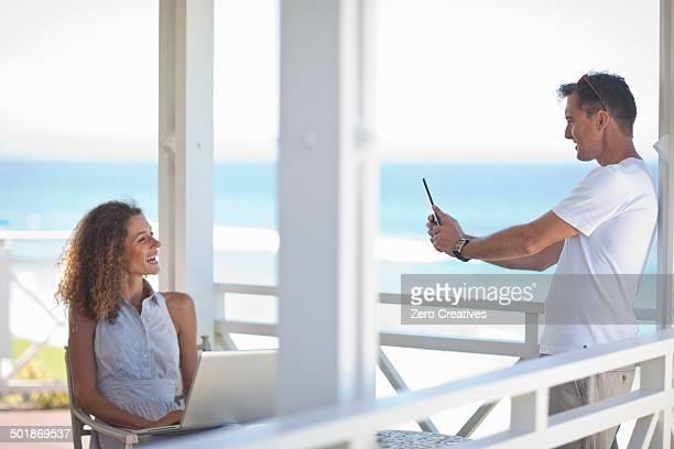 Couple taking photographs on beach house balcony